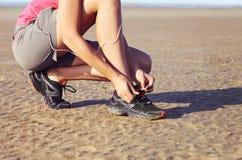 栓鞋带的少妇赛跑者 库存图片