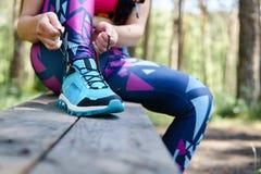 栓鞋带的母赛跑者在公园 健康生活方式 库存图片