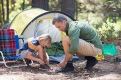 栓鞋带的父亲和儿子由帐篷在露营地 免版税库存图片