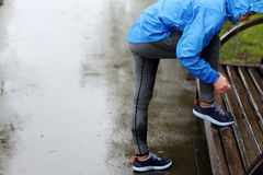 栓鞋带的赛跑者妇女在训练在雨中前 马拉松 免版税图库摄影