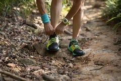 栓鞋带的足迹赛跑者在早晨森林里 图库摄影