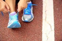 栓鞋带的年轻健身妇女 免版税库存图片