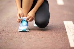 栓鞋带的年轻健身妇女 库存图片