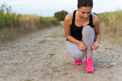 栓鞋带的年轻运动的妇女户外 库存照片