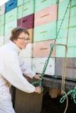 栓绳索的蜂农到在卡车装载的条板箱 库存照片