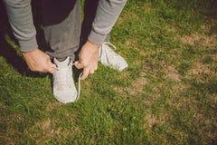 栓他的跑鞋的都市慢跑者 库存图片