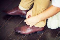 栓他的鞋带的一个人 免版税库存照片