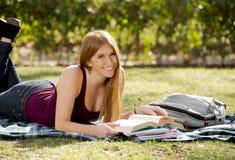 校园与书学习在教育概念的公园草的年轻美丽的学生女孩愉快的准备的检查 免版税图库摄影