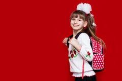 校服和白色的一个逗人喜爱的smilng小女孩鞠躬与在红色背景的一个背包 回到学校 库存照片