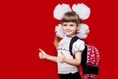 校服和白色的逗人喜爱的微笑的小女孩鞠躬与在红色背景的背包 回到学校 免版税库存照片