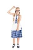 戴校服和眼镜的十几岁的女孩拿着膝上型计算机。 抓他的有笔的女孩头。 库存图片
