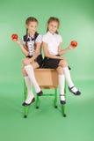 校服的两个女孩坐书桌和吃苹果 免版税图库摄影