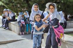 校服的伊朗女小学生在城市, Shir附近的步行的 图库摄影
