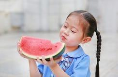 校服的可爱的矮小的亚裔儿童女孩喜欢吃西瓜 库存图片