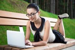 校服的女孩使用说谎在长凳的膝上型计算机在公园 免版税库存照片