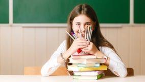 校服的女小学生在她的有书和铅笔的书桌坐一个绿色委员会的背景 免版税库存图片
