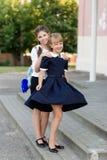 校服的女小学生基于断裂在学校附近 免版税图库摄影