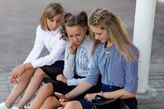 校服的女小学生基于断裂在学校附近 免版税库存照片