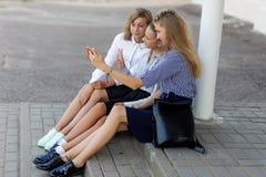 校服的女小学生基于断裂在学校附近 库存照片