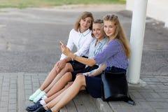 校服的女小学生基于断裂在学校附近 免版税库存图片