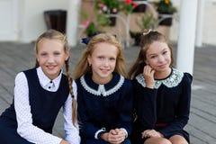 校服的女小学生基于断裂在学校附近 库存图片