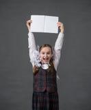 校服的女婴有白色的鞠躬微笑 免版税图库摄影