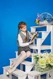 校服阅读书的十几岁的女孩 免版税库存图片