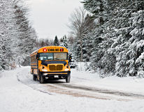 校车压低一条积雪的农村路的- 2 图库摄影