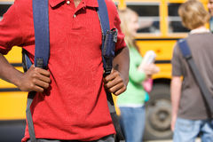 校车:等待乘公共汽车的学生 库存照片