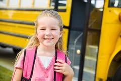 校车:逗人喜爱的女小学生乘公共汽车 库存图片