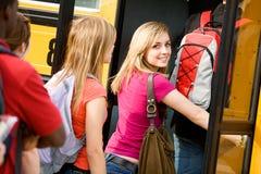 校车:逗人喜爱的青少年的神色,当上公共汽车时 图库摄影