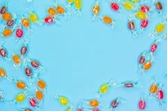 样式棒棒糖,在五颜六色的白色框架背景,顶视图平的位置的糖果 库存图片