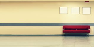 样式简单派 红色沙发,室内设计,办公室 倒空有一个现代红色沙发的候诊室在门和三empt前面 免版税库存照片