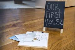 绘样片并且安置在地板上的计划与第一个房子标志 图库摄影