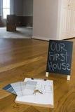 绘样片并且安置在地板上的计划与第一个房子标志 库存图片