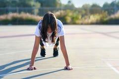 核心身体锻炼-做板条的健身妇女 做板条锻炼的适合女孩室外在体育场内在晴朗的夏日 免版税库存照片