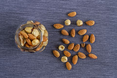 核桃、杏仁和榛子开胃坚果在一个玻璃花瓶在灰色纺织品背景一顿健康快餐的 免版税库存图片
