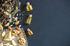 核桃和杏仁的化妆和医疗油在黑背景 免版税库存照片