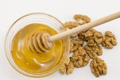 核桃和碗在桌上的蜂蜜 免版税库存照片