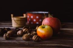 核桃和苹果在土气桌上与老细节对此 免版税图库摄影
