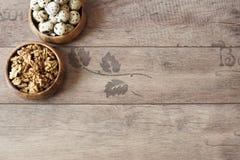 核桃和鹌鹑蛋在木碗 土气木背景,散开的自然光 蛋白质营养素 图库摄影