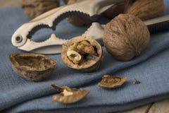 核桃,整个和破裂和在一块蓝色餐巾,分类的一个胡桃钳 库存图片