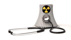核能能源厂和听诊器在白色背景 免版税库存照片