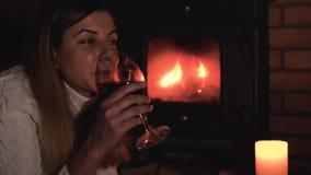 根据壁炉的白种人妇女喝从玻璃的红葡萄酒 股票录像