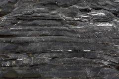 根据岩石纹理的背景  水平地分层堆积,染黑与白色静脉 库存照片