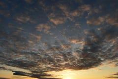 根据日落的多云天空在一个夏天晚上 免版税库存照片