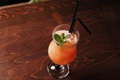 根据杜松子酒的酒精鸡尾酒、樱桃、桔子和利口酒Benediktin,石榴汁糖浆、菠萝和柠檬汁与 免版税库存照片