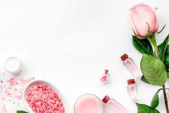 根据玫瑰油的skincare的产品 奶油,化妆水,在白色背景顶视图copyspace的温泉盐 免版税库存图片