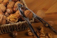 根据篮子的胡桃钳 编辫子的篮子充满坚果:核桃、巴西人、榛子和杏仁 免版税库存照片
