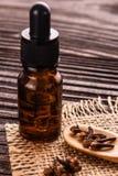 根本丁香油在木土气背景的 免版税库存照片